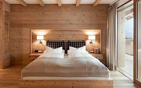 Photo of Camera da letto in legno con letto matrimoniale, lampade laterali accese e porta …