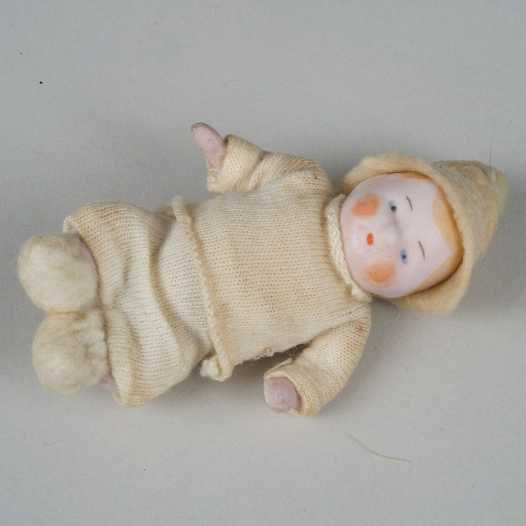 Tiny All Bisque Candy Baby - 2.5 Inches Tall This tiny baby was made in Germany, circa 1925. This unmarked pink tinted bisque baby has a stiff-neck,
