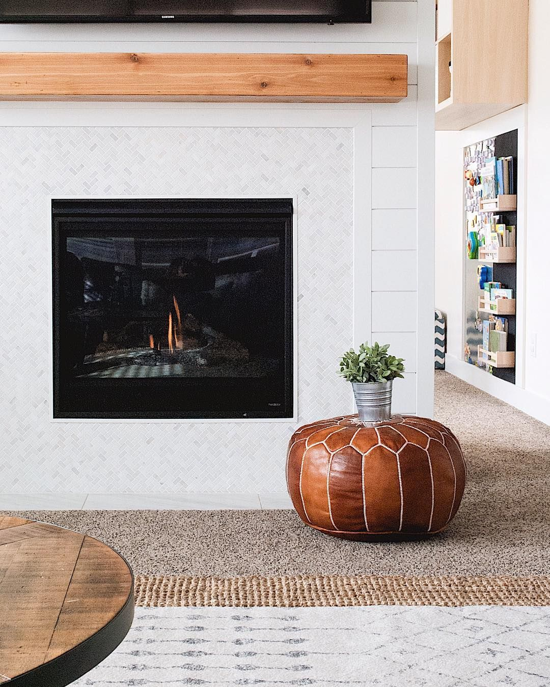 Modern Farmhouse Fireplace With Wood Beam Mantel And Moroccan Pouf