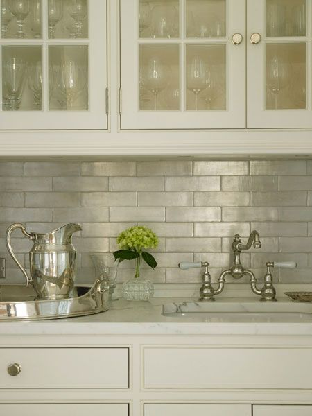 Glass-front upper cabinets and ivory lower cabinets paired with ...