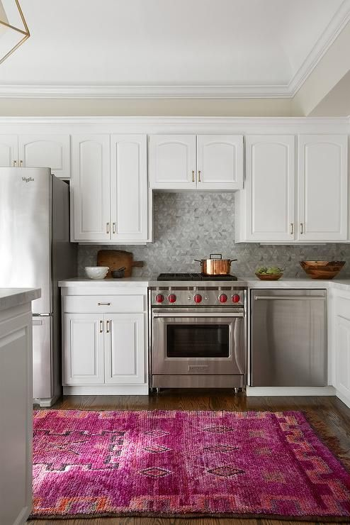 A hot pink kitchen runner leads to white raised panel cabinets ...
