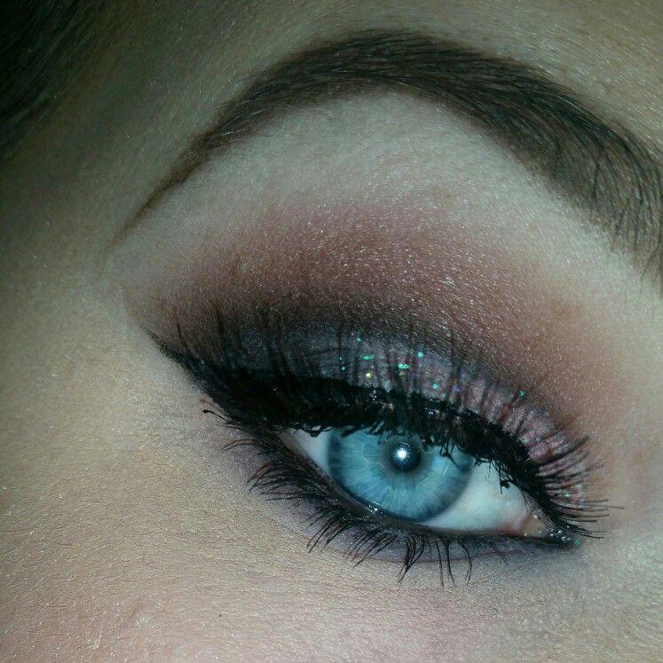 Eye make up with a winged eyeliner, glitter and false lashes