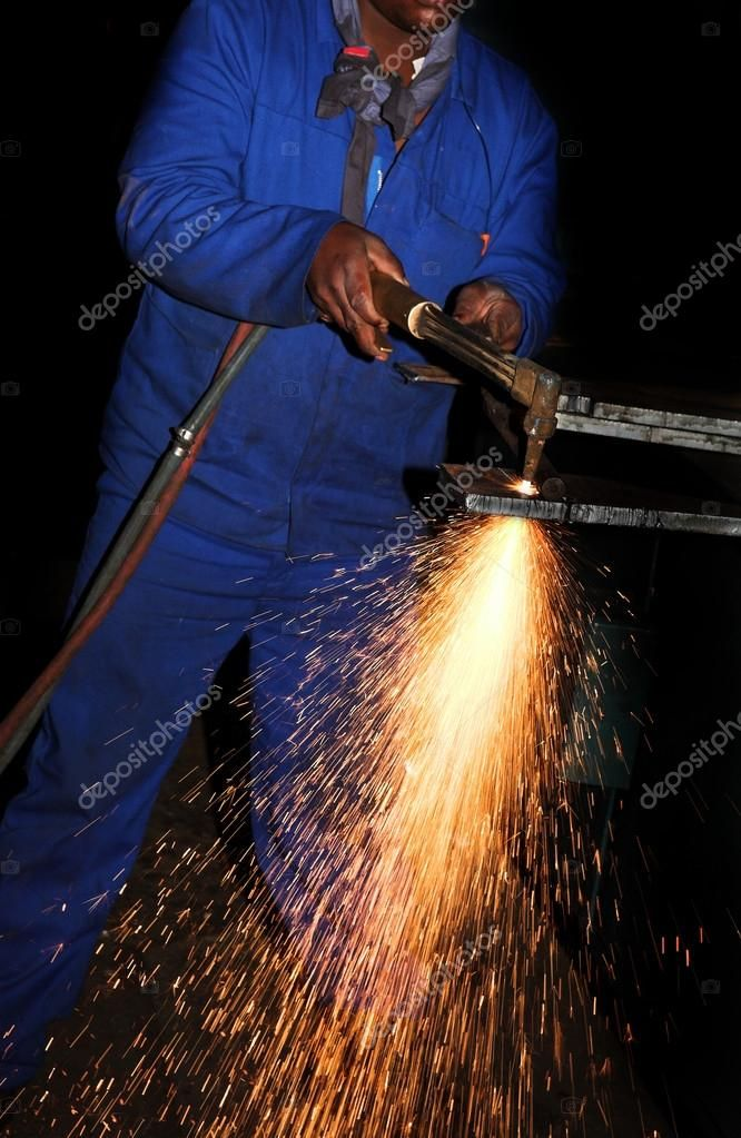 Worker in Blue safety overalls working with Plasma cutter