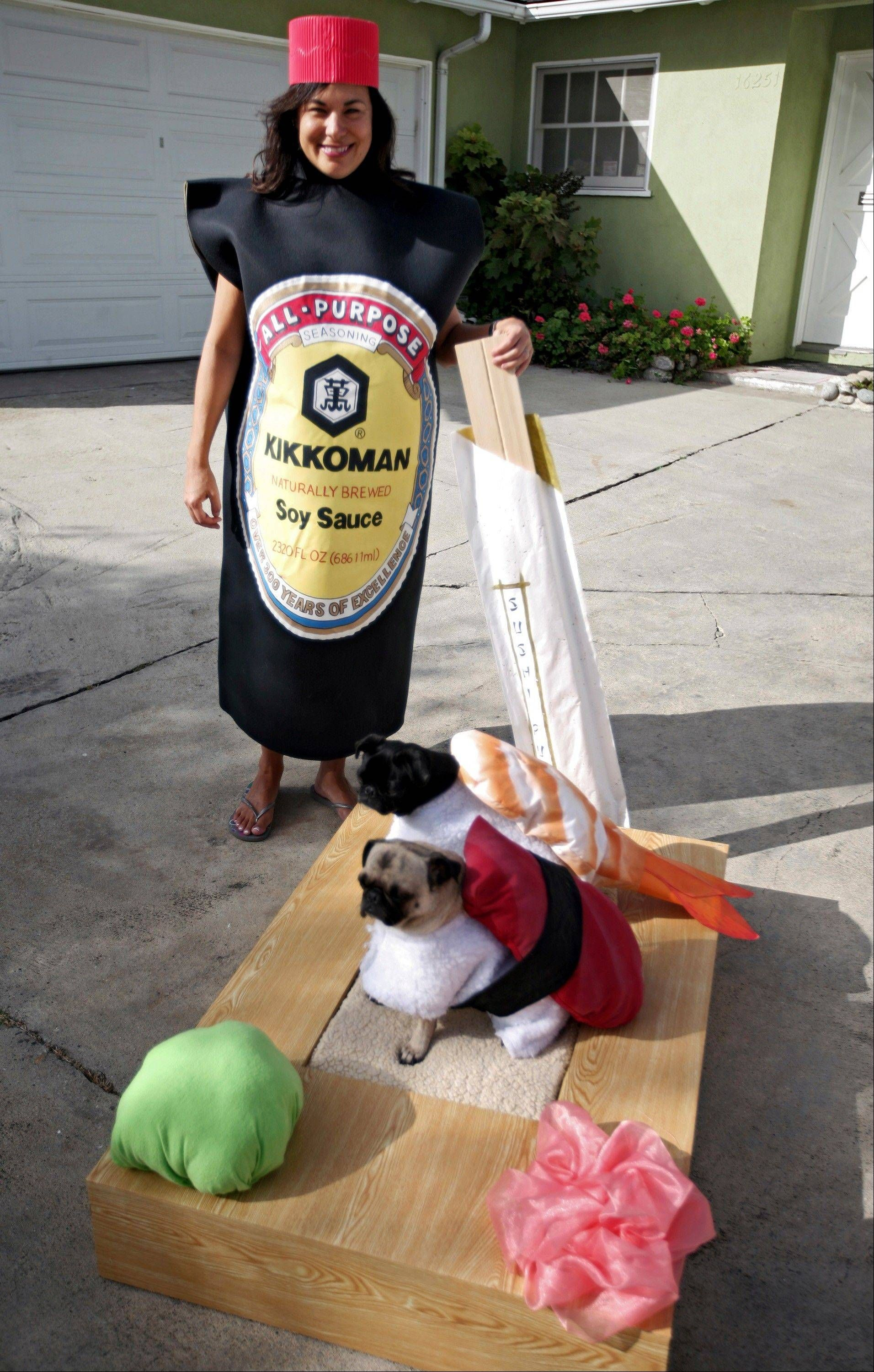 Lisa Woodruff holds a pair of chop sticks alongside her pugs Mochi, foreground, and Olive dressed as sushi at their home in Huntington Beach, Calif.