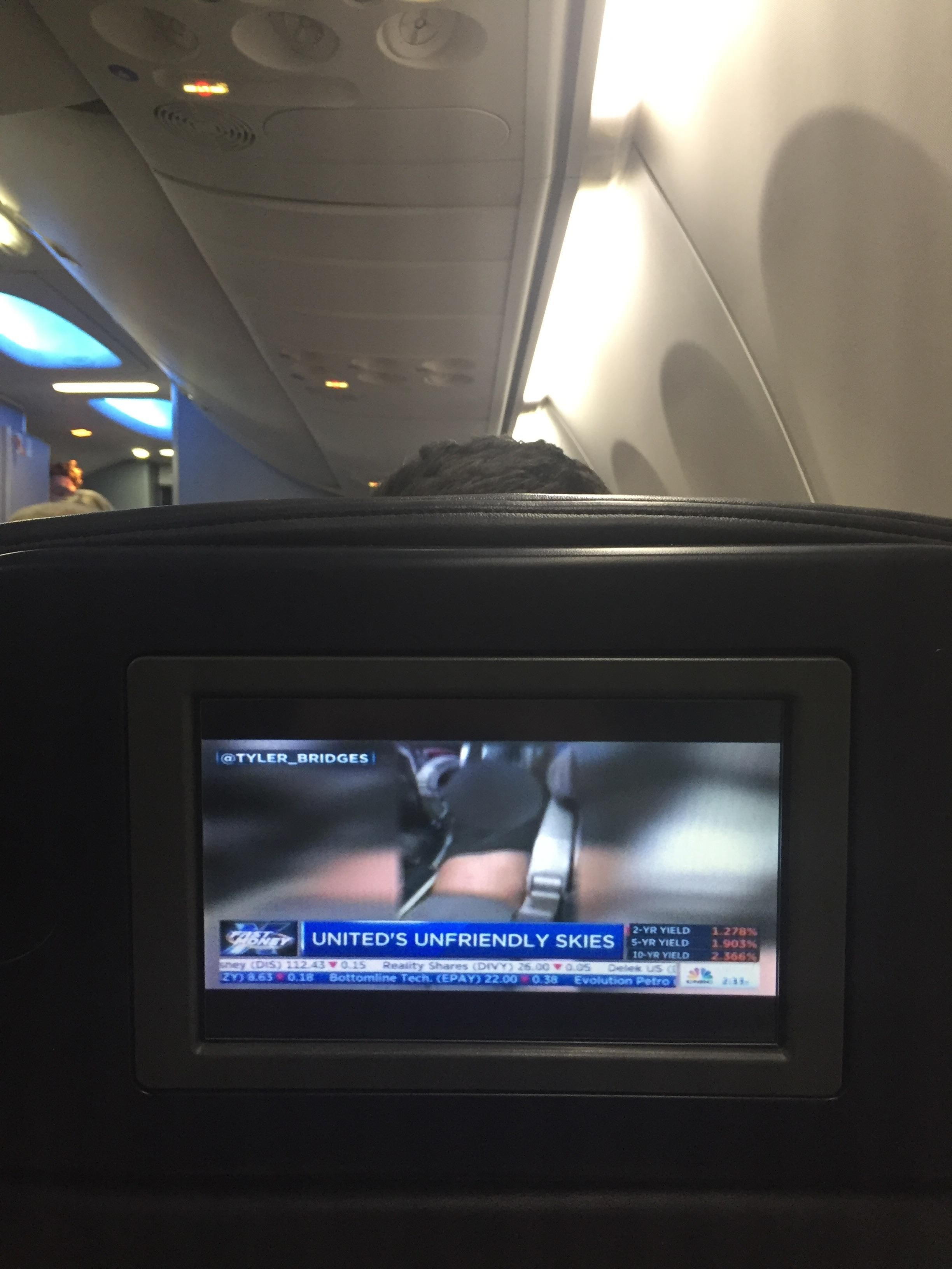 On a United Airlines flight while all the TV's play a newsreport about their own mishap.