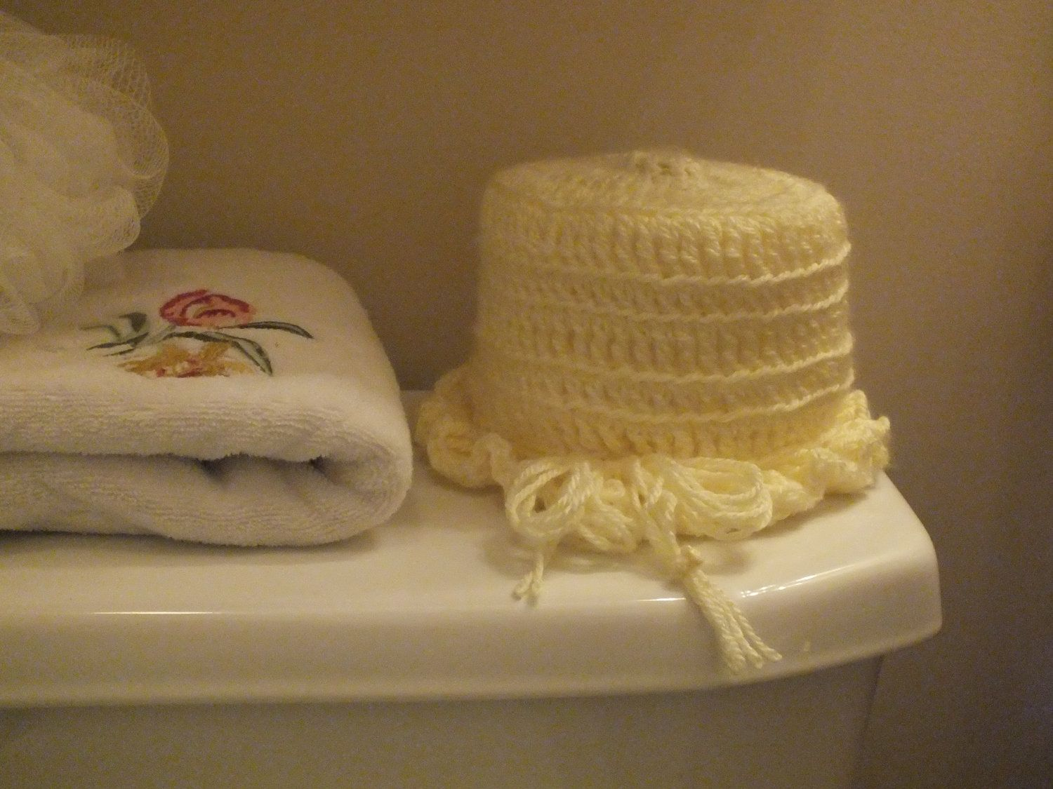 A pale yellow crocheted toilet paper cover by KnotSewKnottyGirls