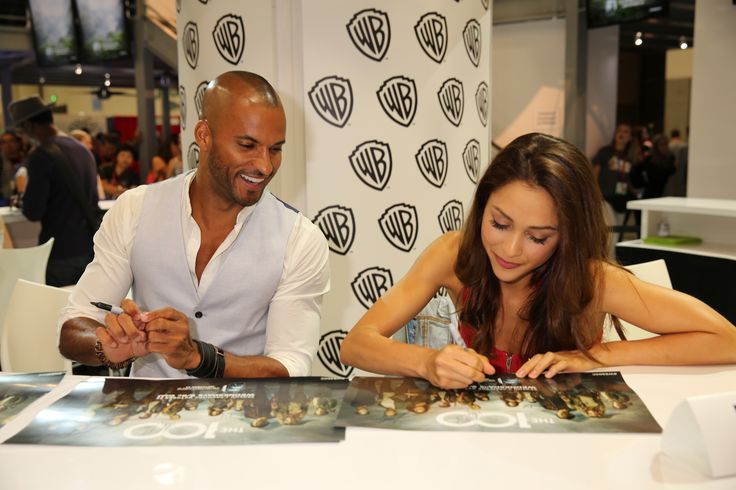 Is he checking her work? THE 100's Ricky Whittle and Lindsey Morgan sign posters of the series for fans at the Warner Bros. booth at Comic-Con 2014. #WBSDCC