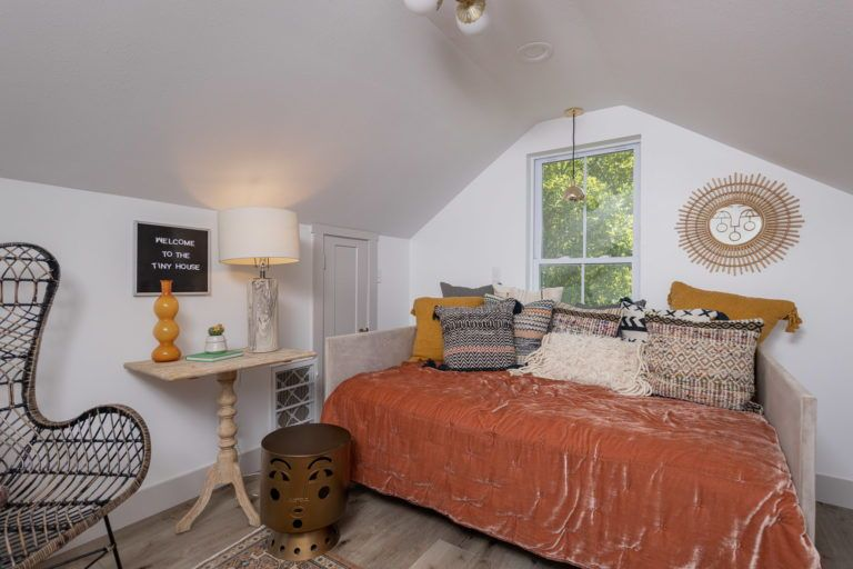 Even in a small home, your bedroom can feel spacious and comfortable! This second-story room combines cozy bedroom vibes with sleek, curated furniture and accessories. Click for a full tour of this amazing tiny home!   #bedroom #orangeduvet #bed #tinyhome #tinyhouse #smallbedroom #renovation #bedroomdesign #cozybed #cozybedroom #indetailinteriors #bedroomfurniture #pillows #bedsidetable #smallroomdesign