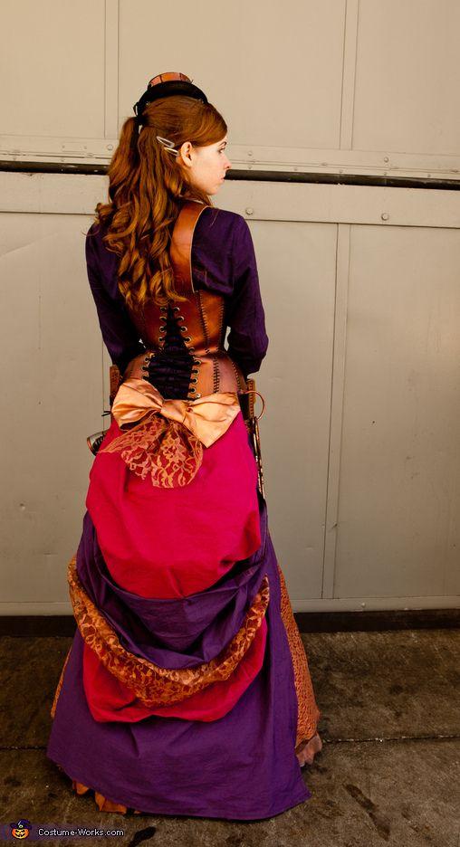 hair style, mini hat, corset lacing, jewel tone dress, painted nerf gun