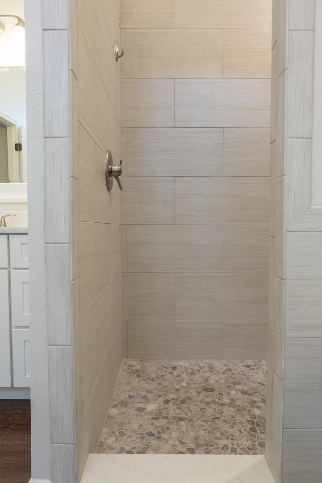 Lindross remodelingcoastal custom homes1gndhgtvcom pebble shower floor sleek yet soft gray tiles carve out a gorgeous walk in shower in this transitional bathroom pebble tile floors in gray tones coordinate dailygadgetfo Images