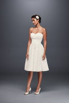A short and sweet lace wedding dress, beautifully pleated at the sweetheart bodice before flowing into a flowing, knee-length skirt by Galina available at David's Bridal