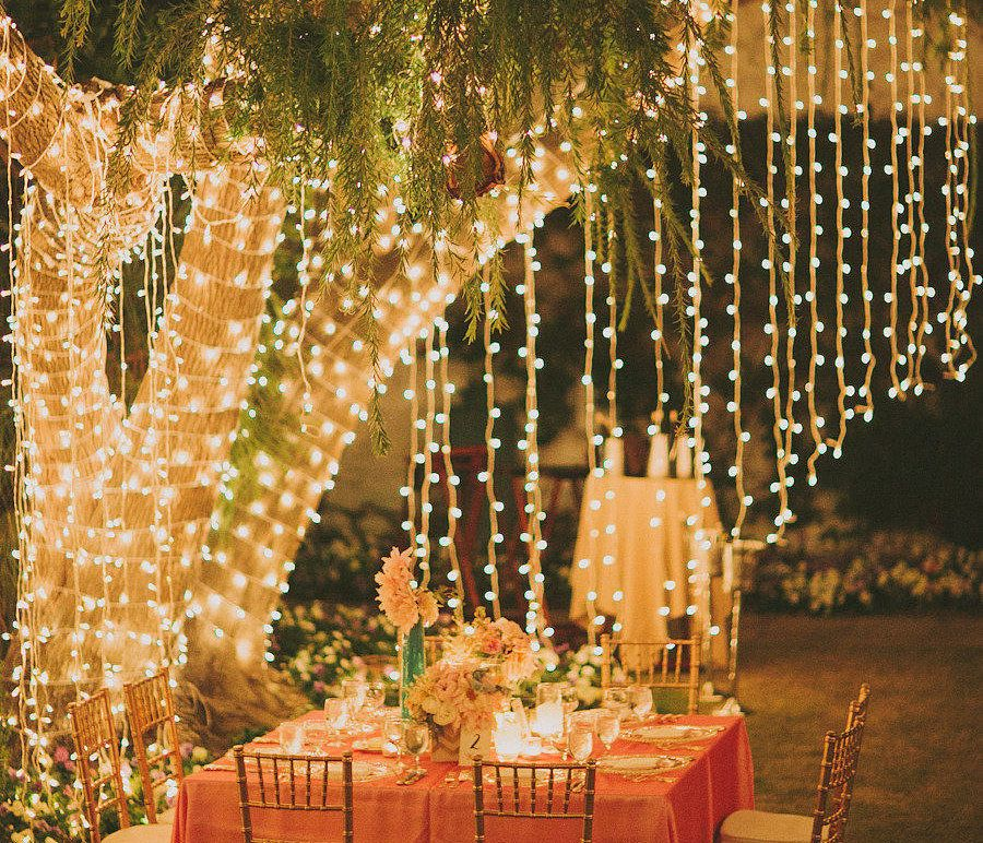 String Lights Hanging From Tree Branches Around A Dinning Table Create An Intimate Romantic Place