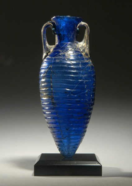 ROMAN COBALT BLUE GLASS AMPHORISKOS    Mold-blown, the ovoid body with concentric horizontal ridges and a pointed base, with a cylindrical neck, flaring mouth, the rim folded out then in, and twin vertical handles.    Later 1st Century AD    H. 4 1/4 in. (10.8 cm.)