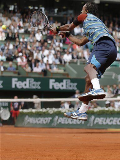 Gael Monfils of France jumps to return against Tomas Berdych of the Czech Republic in their first round match of the French Open tennis tournament, at Roland Garros stadium in Paris, Monday, May 27, 2013.