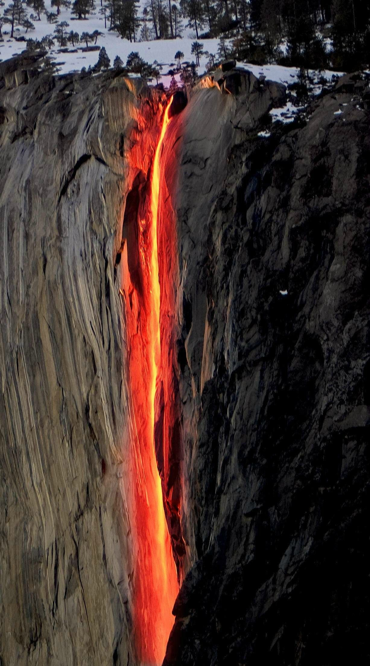 """Horsetail Fall in California flows only in winter and spring. Most days of its 'life' this fall has a regular color. But every February, just for a couple of days, this fall turns into the fire. Lit by the sun, Horsetail Fall reflects orange and red rays."""