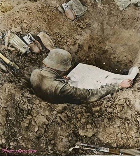 German soldier reading a newspaper in his foxhole on the Eastern Front. 1941. --------------------- Soldat allemand retranché dans un Foxhole lisant le journal sur le Front de L'Est. 1941