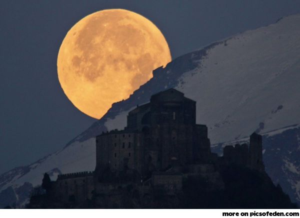 A full moon sets behind the Alps