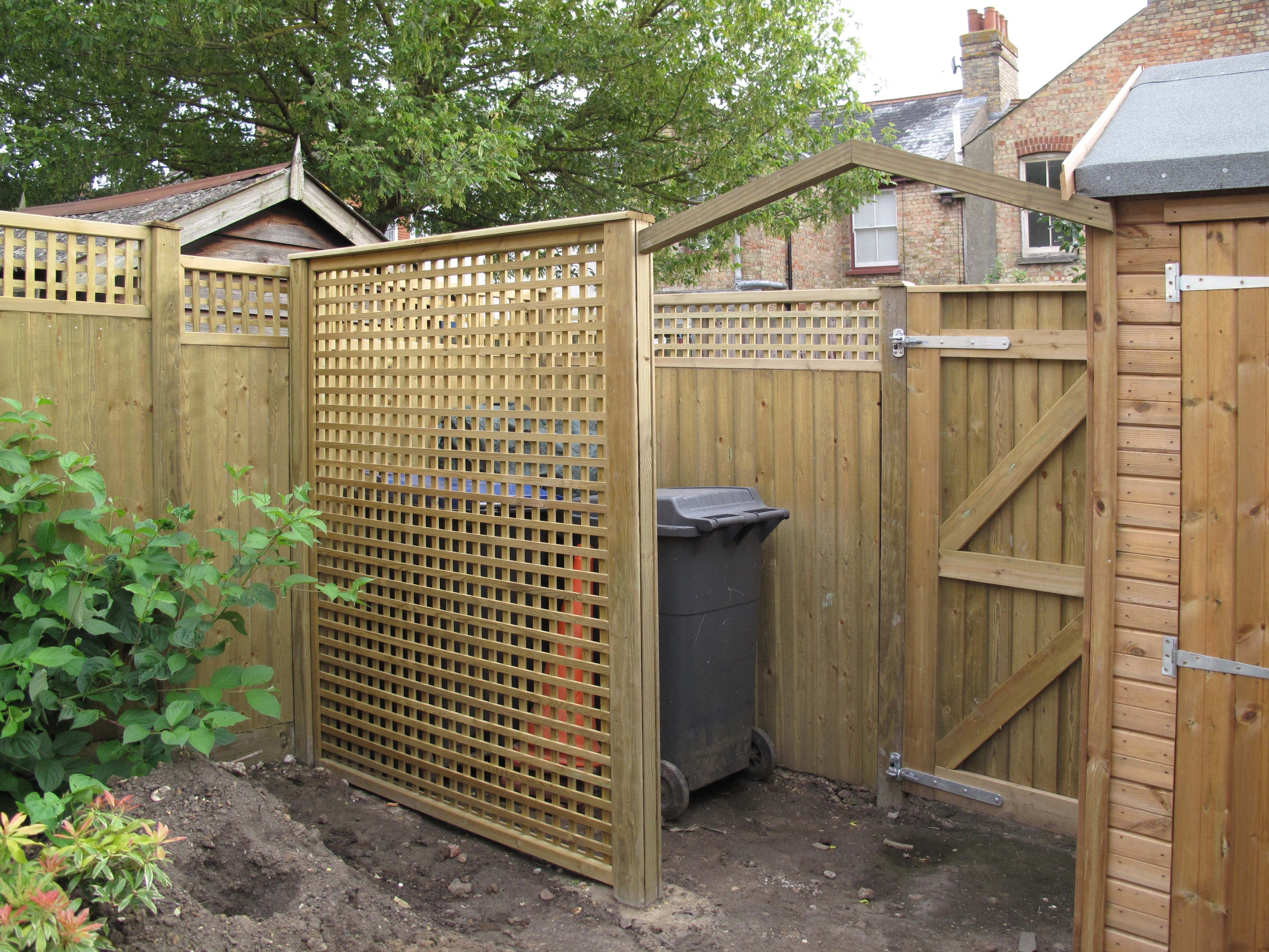 full height lattice trellis panel installed at right angles to the fence which creates a clever hide for the numerous wheelie waste and recycling bins