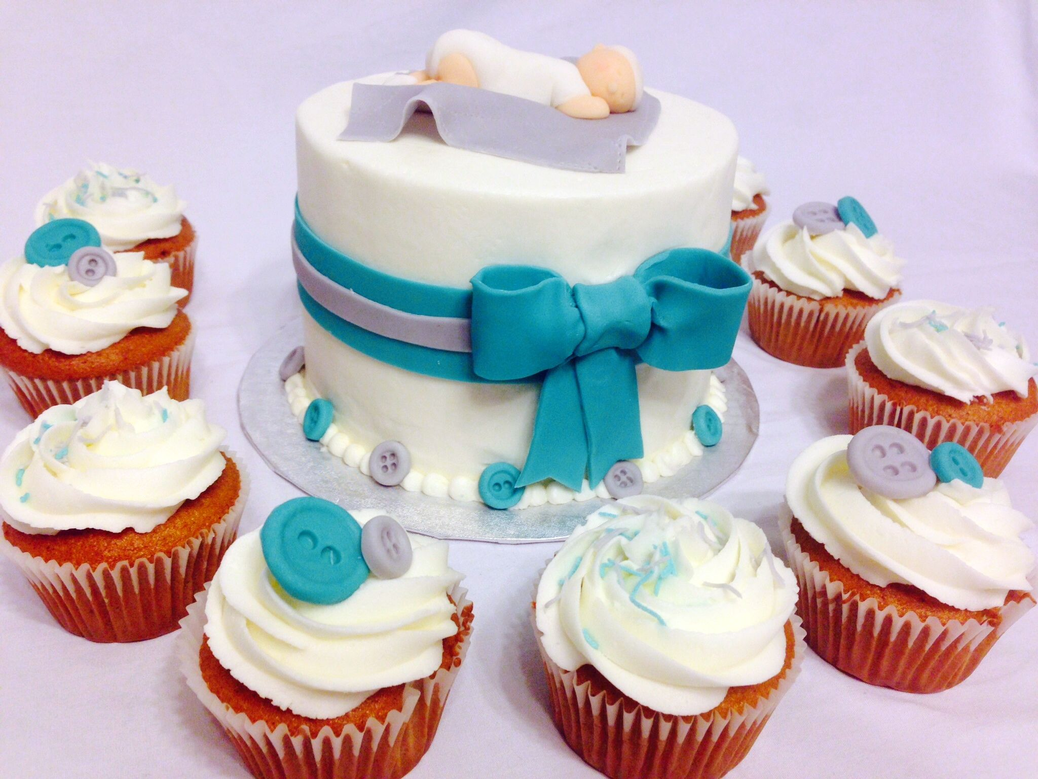 baby shower cake with cute fondant buttons and cupcakes.