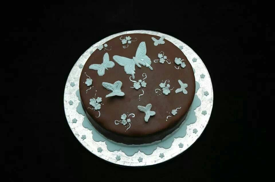 """8"""" round chocolate cake decorated with blue butterflies."""