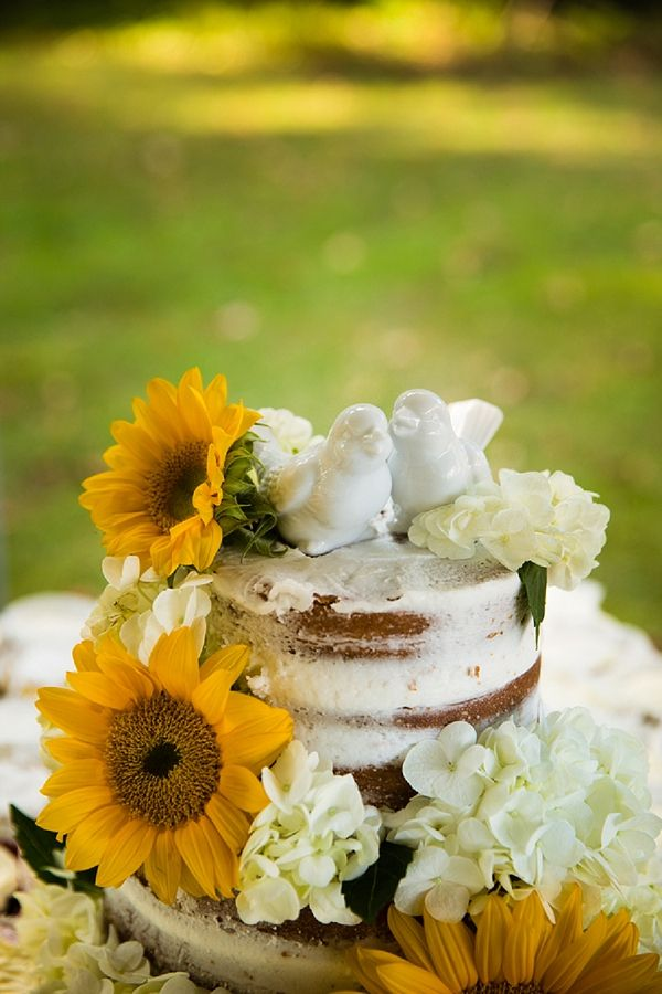 Rustic naked cake with a lovebirds cake topper and sunflowers