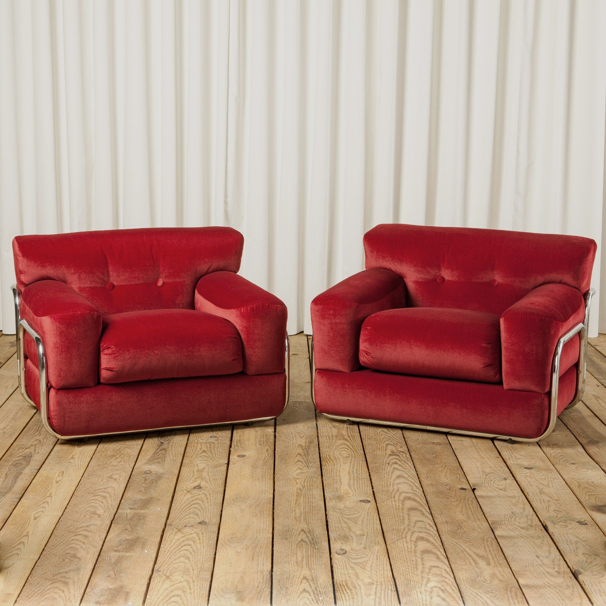 A pair of 1970s chrome framed lounge chairs upholstered in