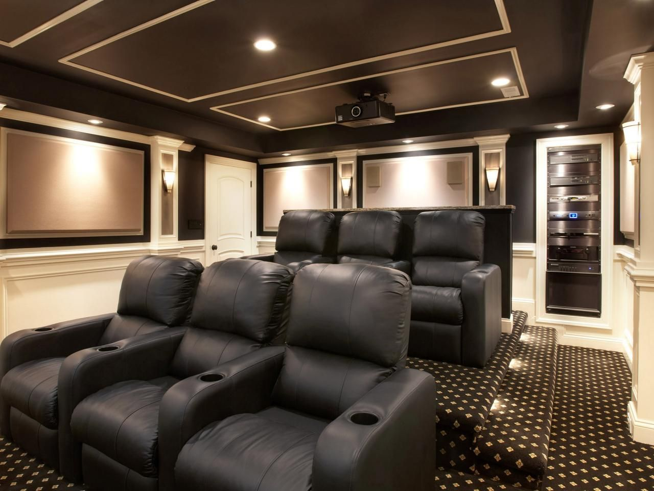 Movie Theater Room With Two Level Tiered Floor Black Recliners Steps Carpet Built In Electronic Equipment The Wall Projector On Ceiling