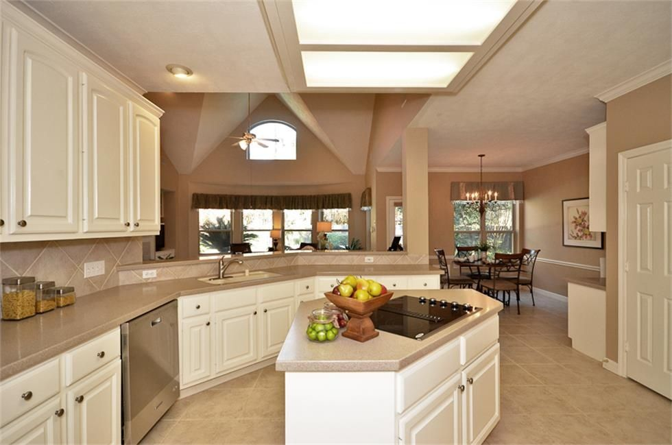 Traditional Kitchen with Kitchen island, Chandelier, Columns, Limestone Tile, limestone tile floors, High ceiling, L-shaped