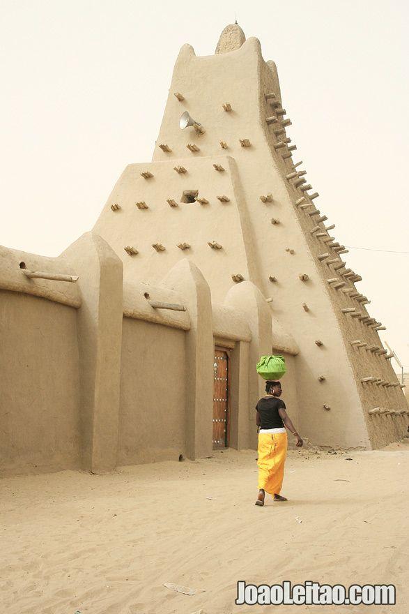 Woman walking aside Sankore Mosque - Travel to Timbuktu