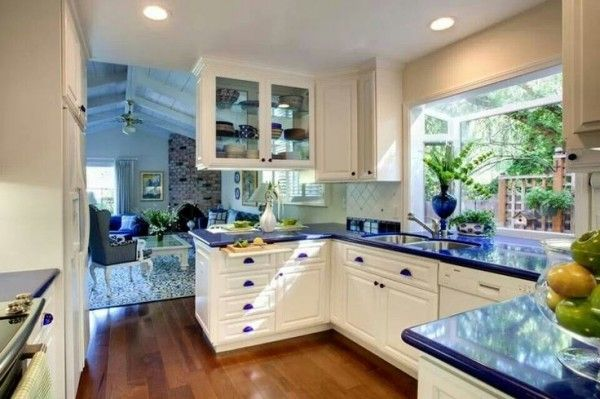 Kitchen Blue Corian Countertops Below Clear Glass Pedestal Fruit Bowl Also Protruding Window Frames Toward Small
