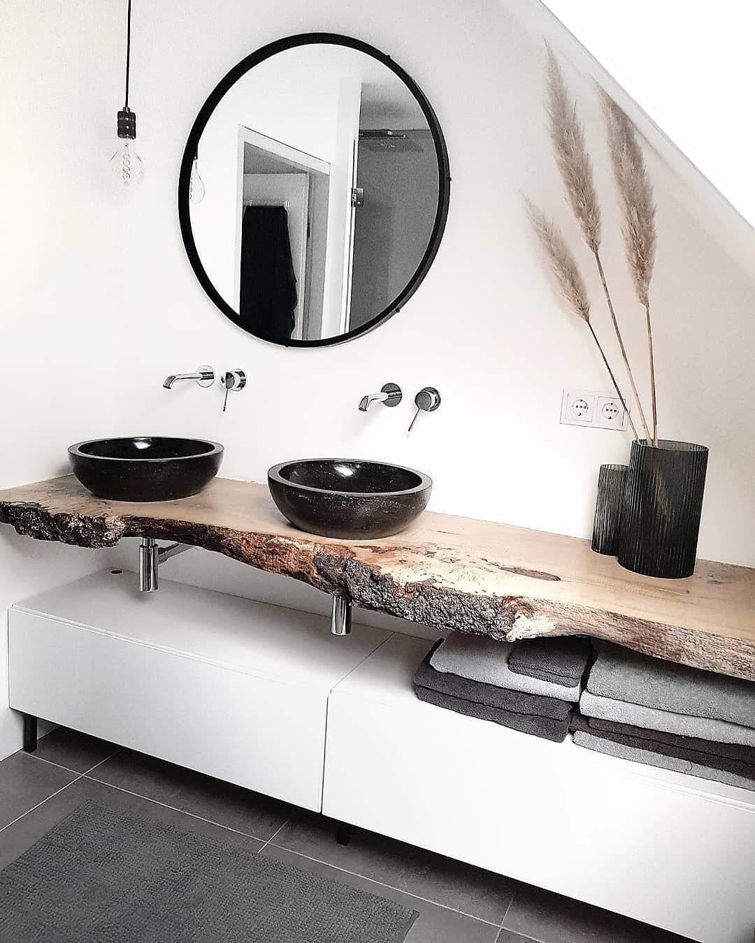Photo of Deze badkamer heeft een asymmetrische balans doordat de zwarte wastafels …