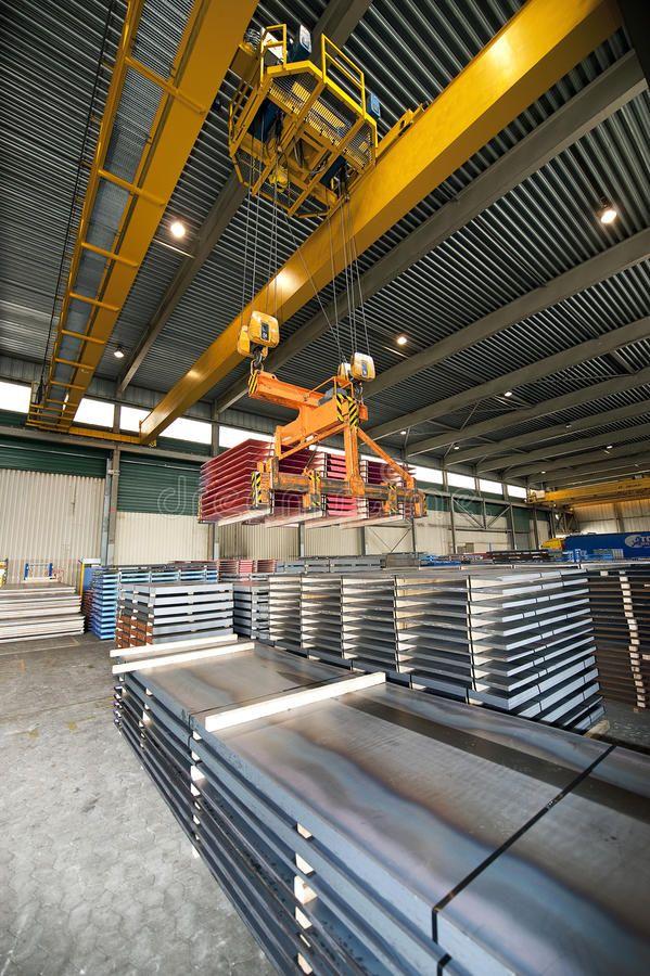 Handling Steel Huge overhead crane handling pallets containing steel sheet at