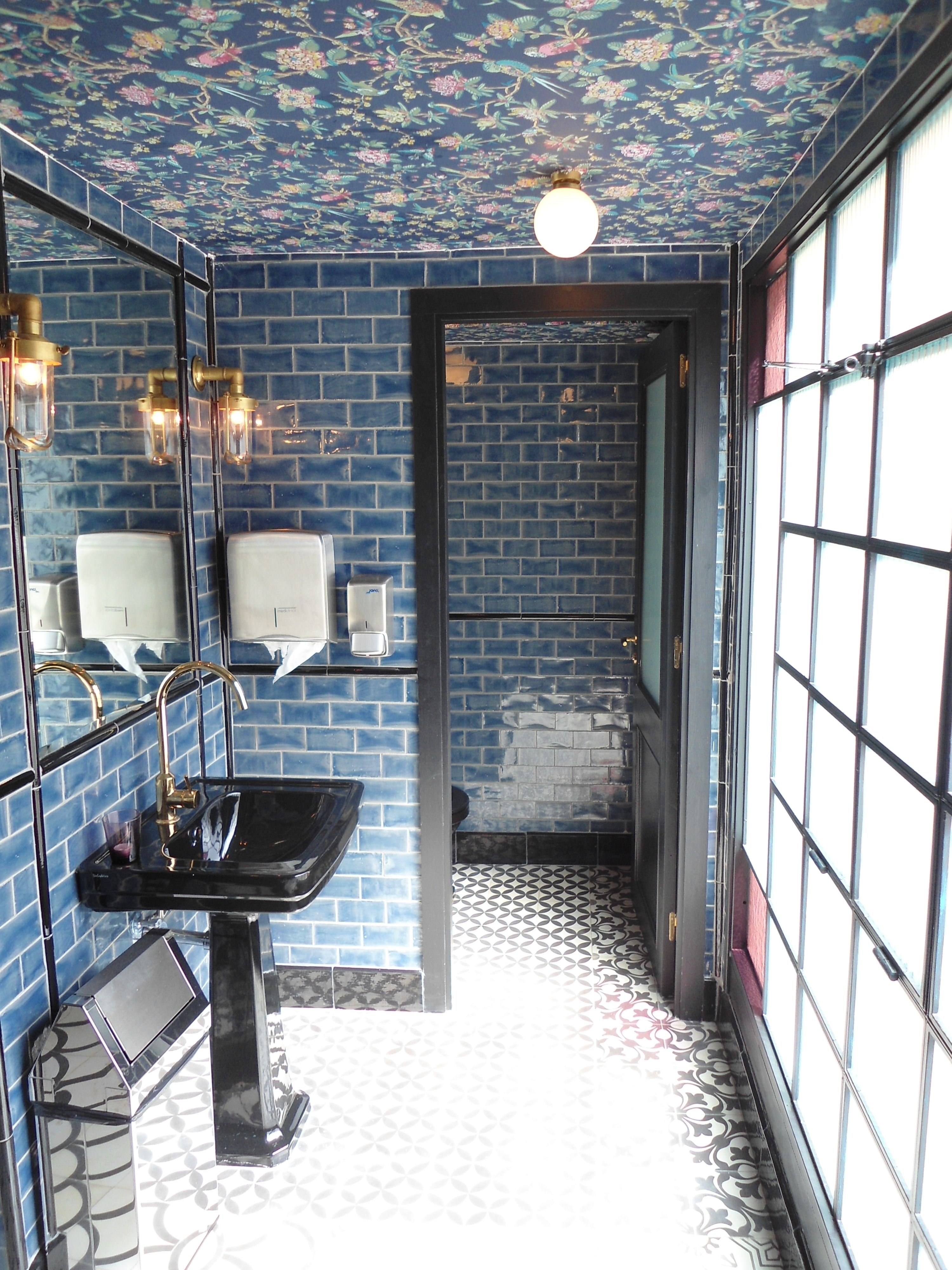Subway tile, wallpaper on the ceiling, and a brass faucet
