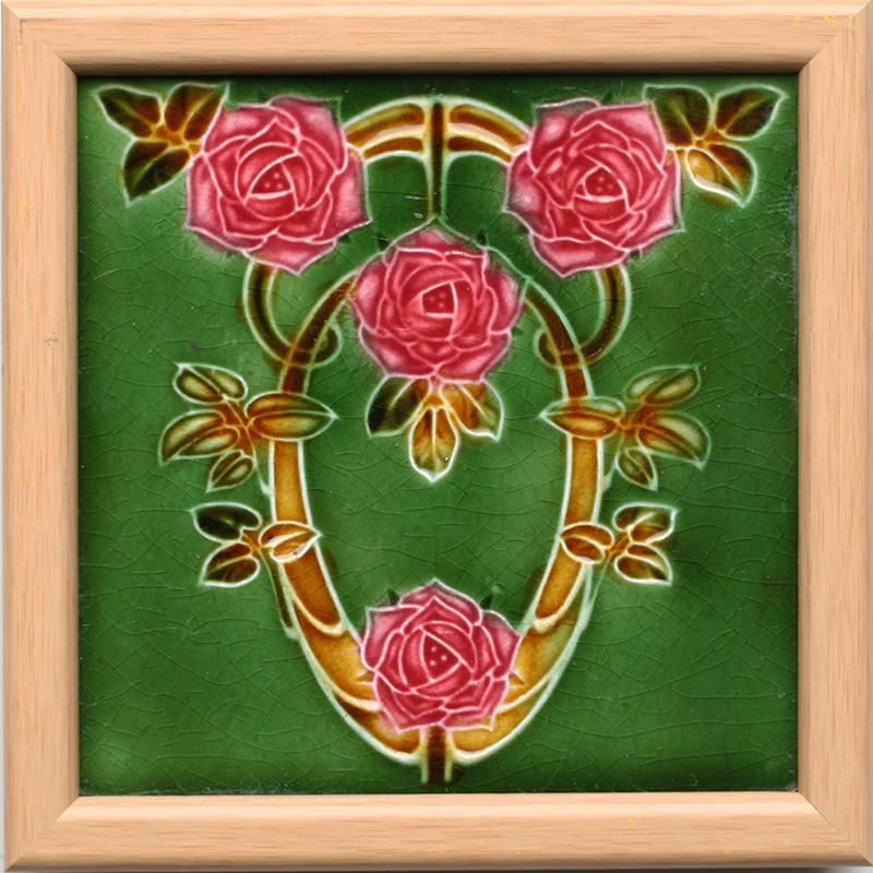 A mid green ground Art Nouveau tile, with a stylised four rose head, leaf, and stem design in dark pink...