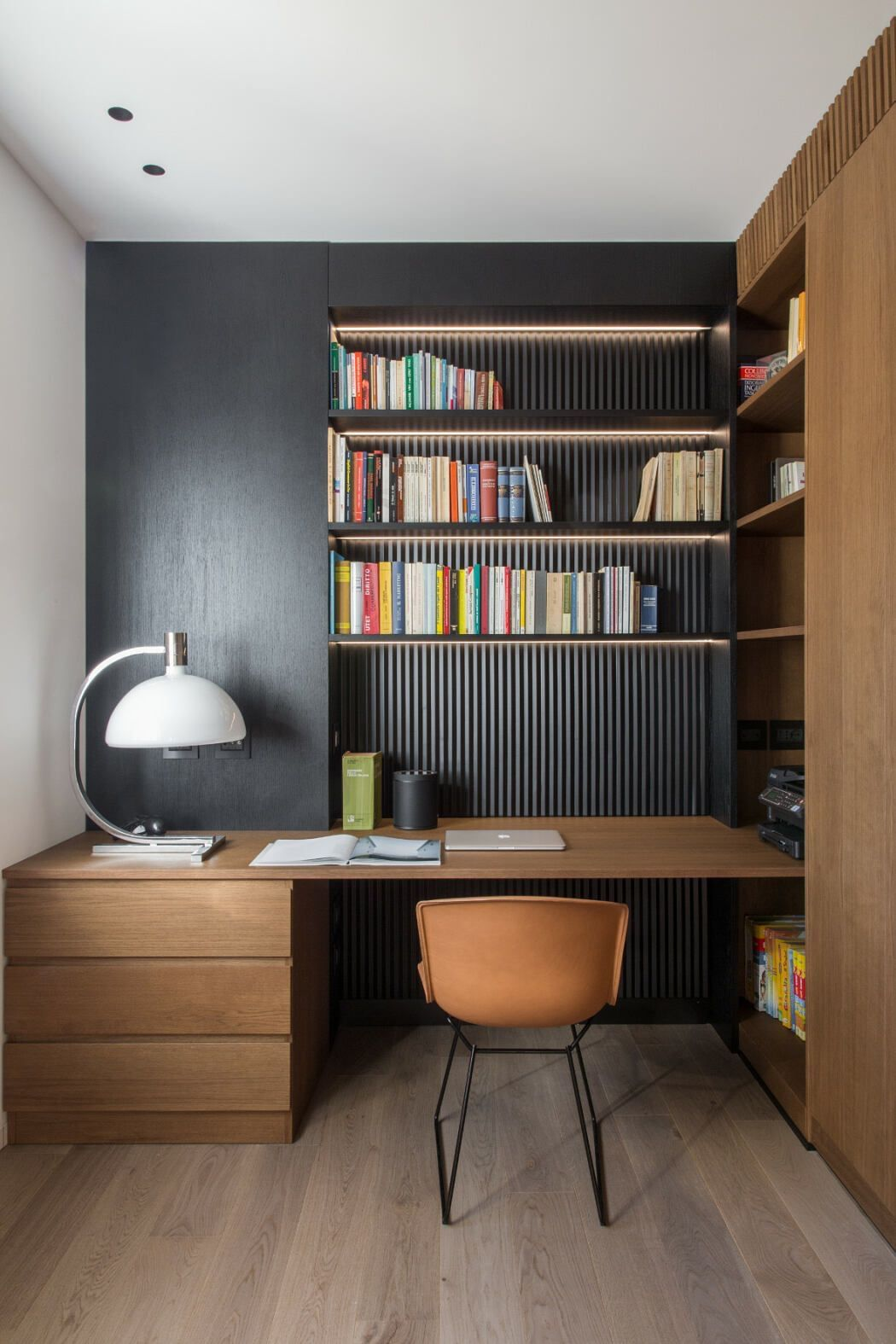 Home Office With Dark Walls Book Shelves And Furniture In Teak