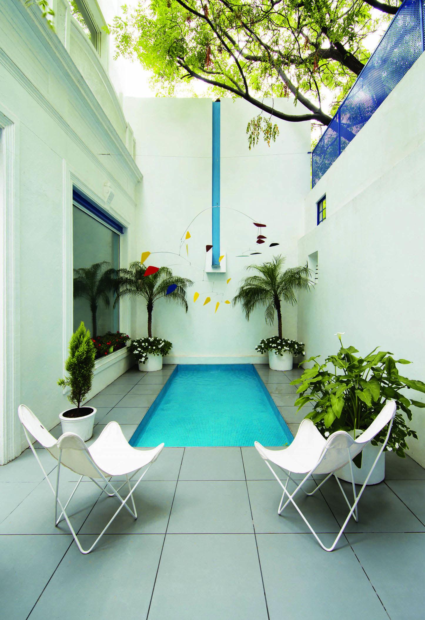 Un patio donde cuelgan m viles del estilo de los de calder for Patios de casas modernas con piscina