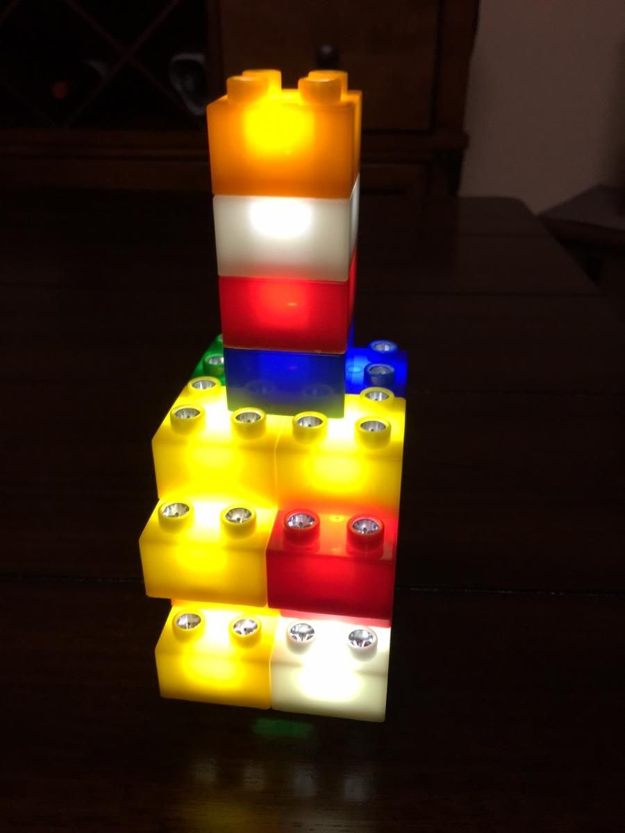 different lego blocks with lights inside of them built into a tower