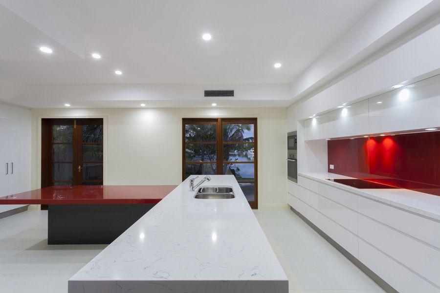 cocina moderna decorada en colores blancos y rojos con isla en medio iluminacin con