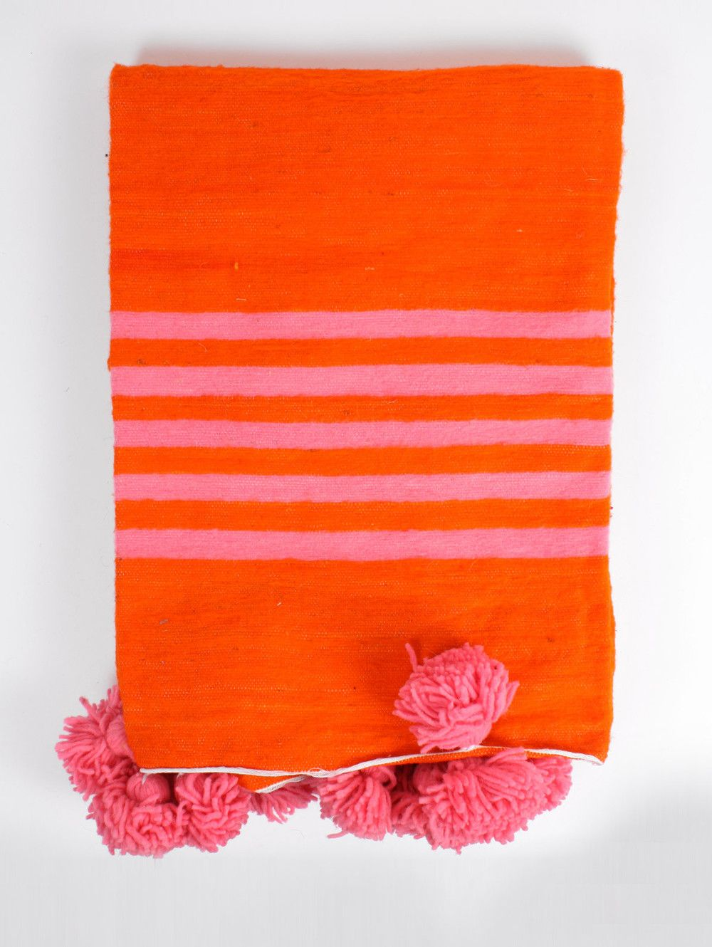 A traditional handwoven Moroccan throw in bright orange with pink stripes  and decorated with beautiful wool pom poms.      * Handwoven in Morocco     * 100%Wool     * Size: Large 2 x 3 m / 6.56'x 9.8' ft