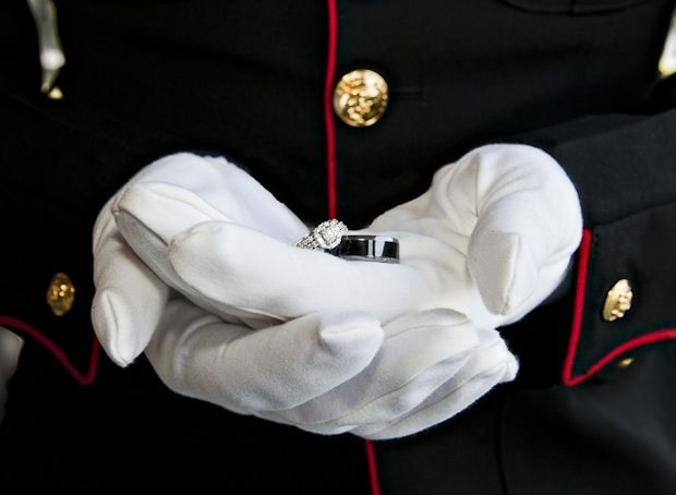 military wedding in red and blue groom holds the rings in his gloved hands - Military Wedding Rings
