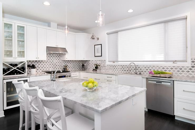 Amazing Kitchen Features White Shaker Cabinets Paired With Super White  Quartzite Countertops And A White And Gray Geometric Marble Backsplash.