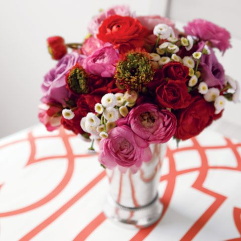 """Fresh, flower market style is brought to life with a lush bundle of lavender garden roses and ranunculus, petite red and petal pink tea roses, and a burst of tiny white buttons. Tucked in a silver tone julep cup, Lottie measures 6"""" x 6"""" x 9"""" and requires next day shipping."""