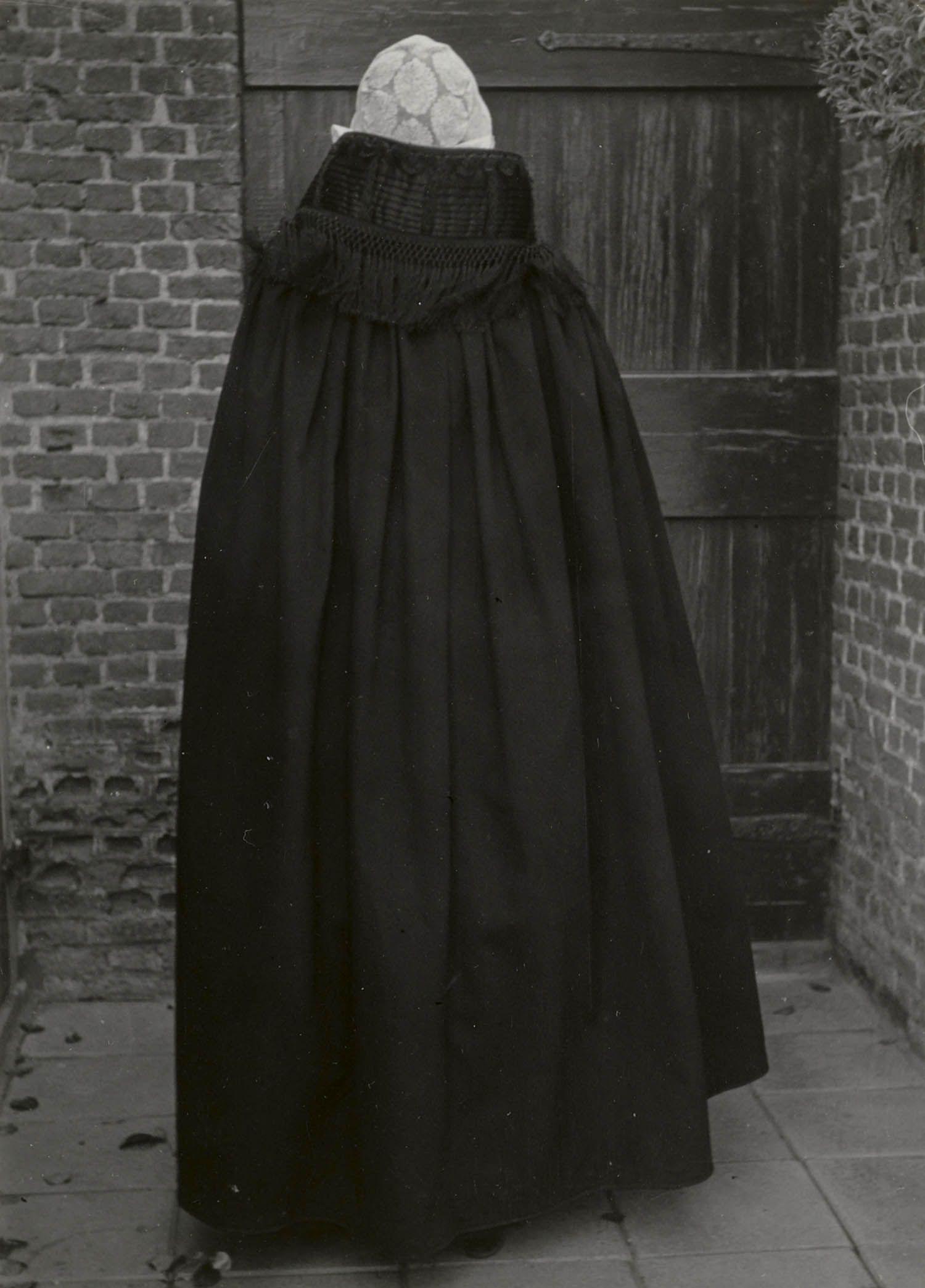 Vrouw in de Cadzandse streekdracht. De vrouw is gekleed in zondagse dracht. Ze draagt op haar hoofd een cornetmuts, met een bol van doorgestopte tule en een voor- en achterstrook van kloskant. Tegen de koude heeft ze een cape omgeslagen. #Cadzand