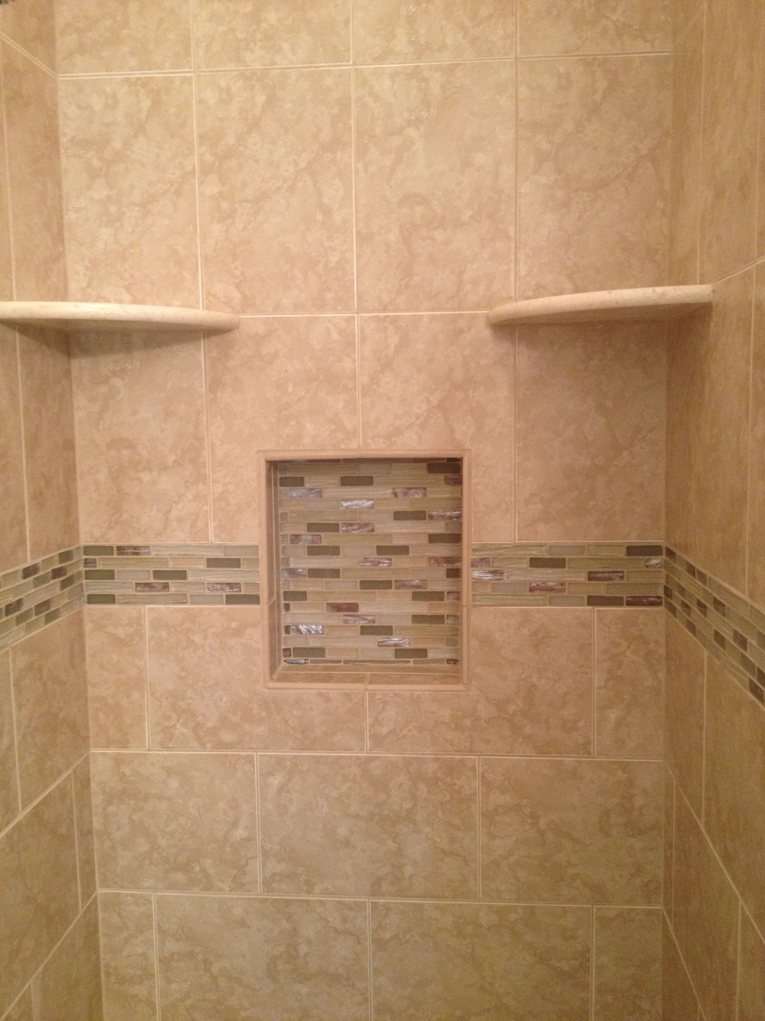 Beige tiled shower with two corner shelves and a niche