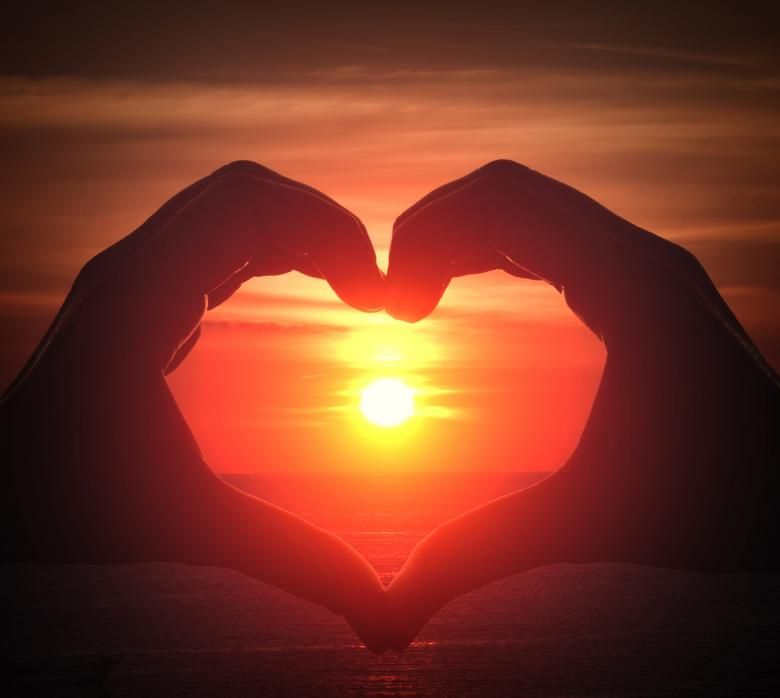 Get Free Stock Photos of Hand silhouette in heart shape with sunset in the middle and oce Online