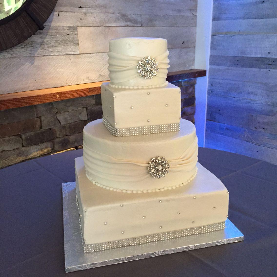 4 tier round and square white buttercream wedding cake with fondant sashes, brooches and bling
