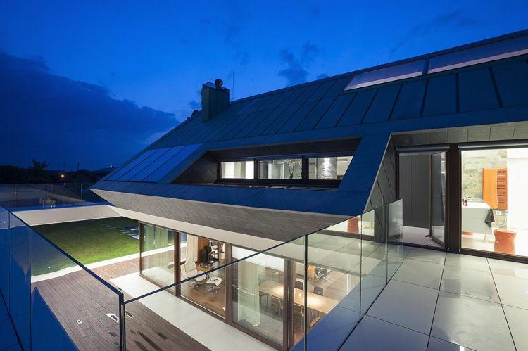 Maison sur terrain en pente avec terrasse et garde corps en verre ...