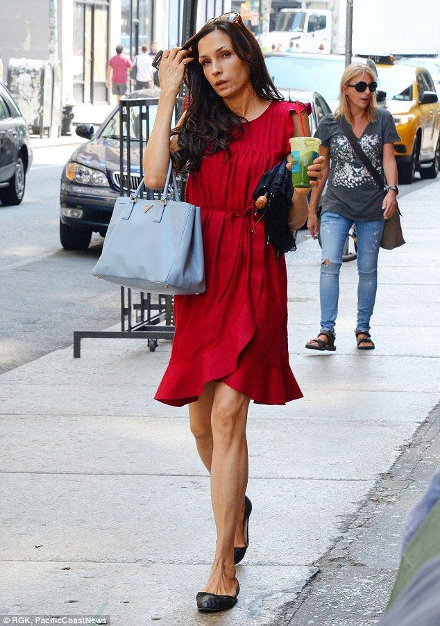 382409f0ef55 Famke Janssen protects her youthful complexion with an umbrella in ...