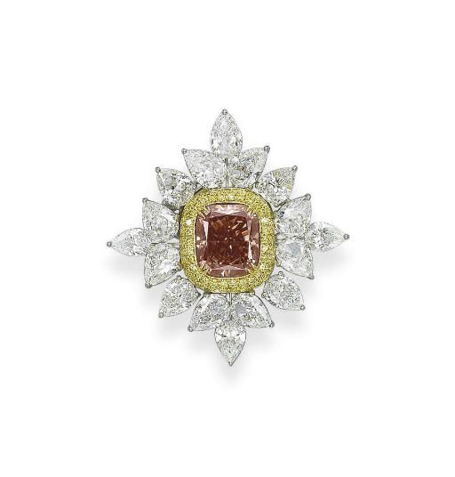 A COLOURED DIAMOND AND DIAMOND PENDANT/BROOCH   Set with a modified cushion-shaped fancy deep brownish pinkish orange diamond, weighing 10.07 carats, within a pavé-set yellow diamond border to the pear-shaped diamond foliate cluster surround, mounted in platinum and 18k gold, 4.4 cm long