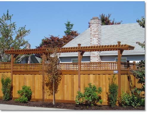 Wooden privacy fence with a tall arbor for added screening for Fence with arbor